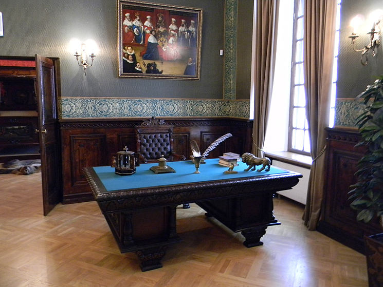 A big historical desk with pen and ink, a big painting in the background