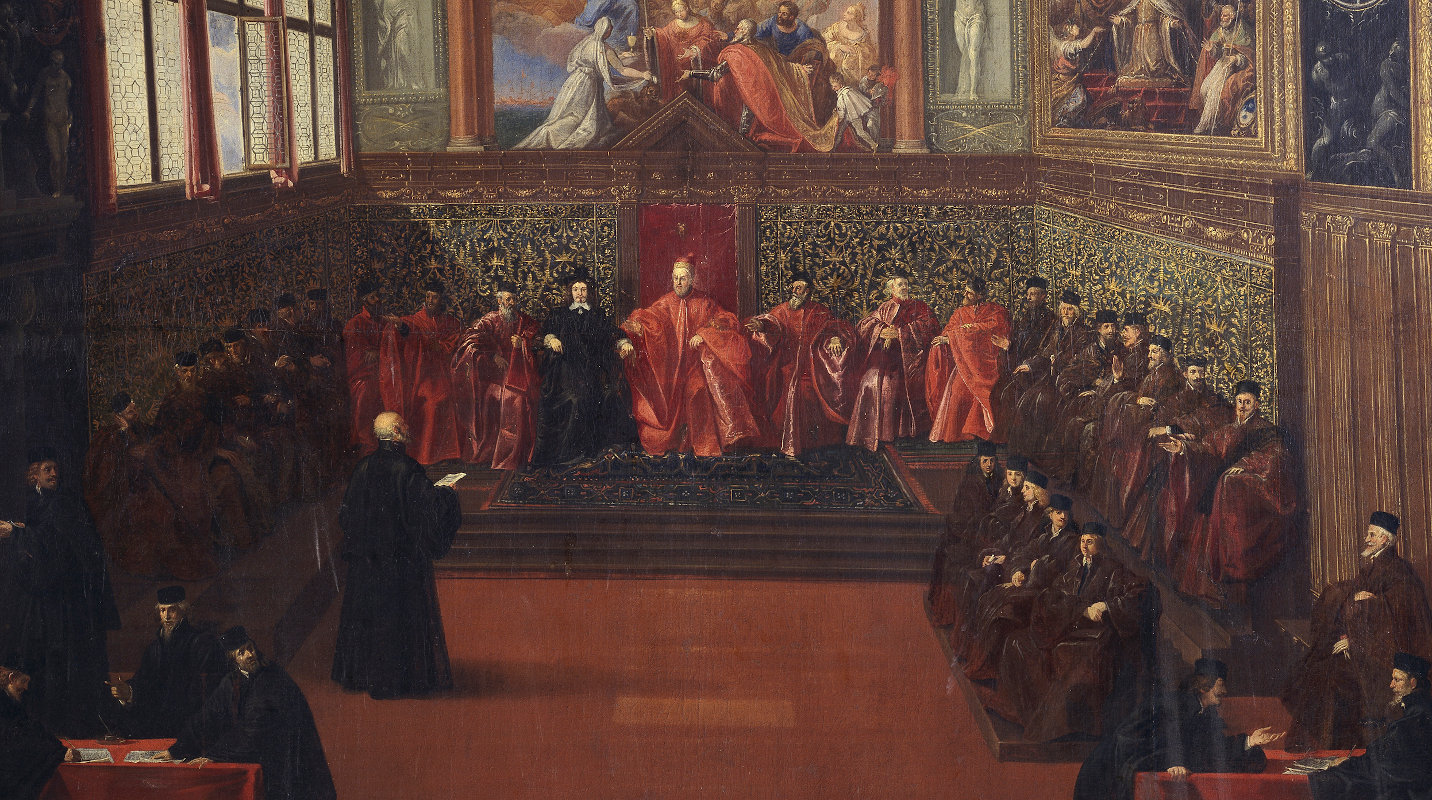 Officials in black and red robes sitting around the standing ambassador in a lushly decorated hall
